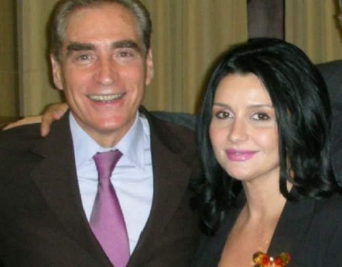 Petre Roman și Silvia Chifiriuc la un eveniment. El poartă un costum maroniu, cu cămașă albă și cravată mov, iar ea un sacou negru.