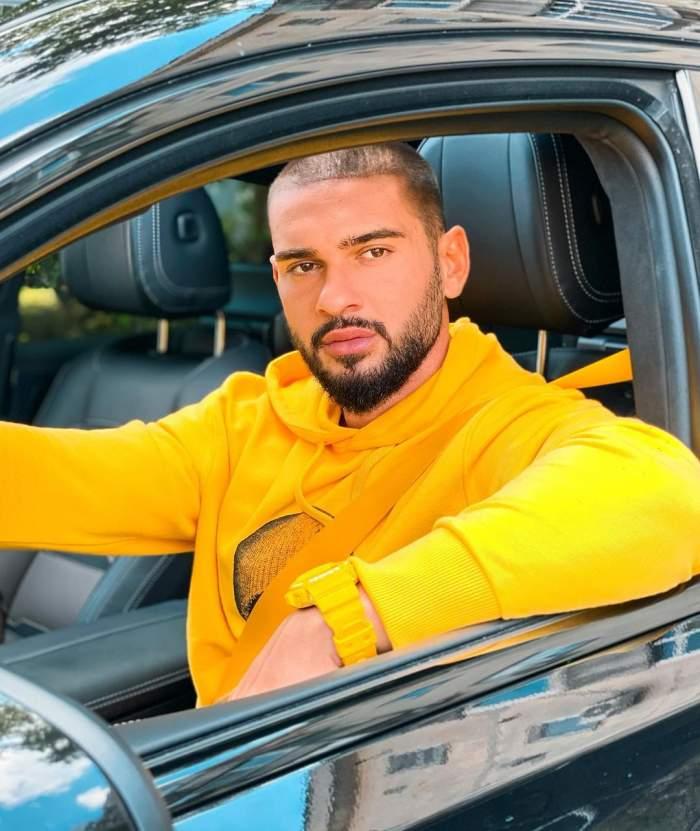 Dorian Popa in hanorac galben la volanul masinii sale.