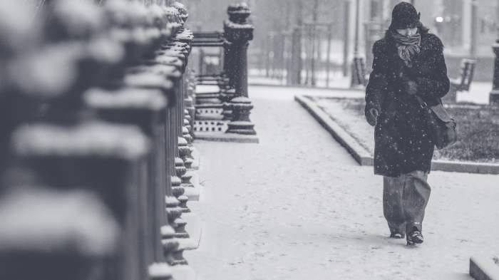 Femeie care merge prin ninsoare