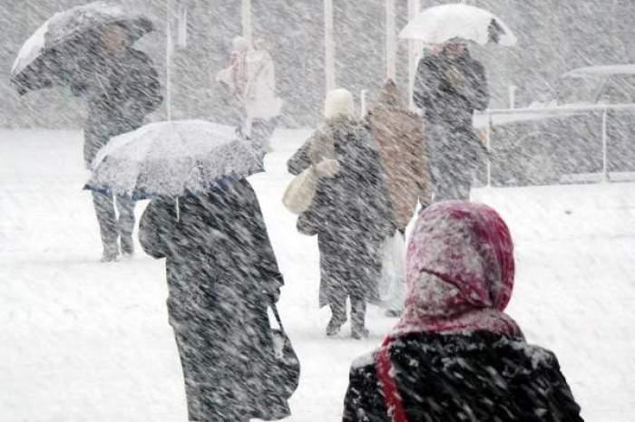 Oameni cu umbrele pe viscol de zăpadă
