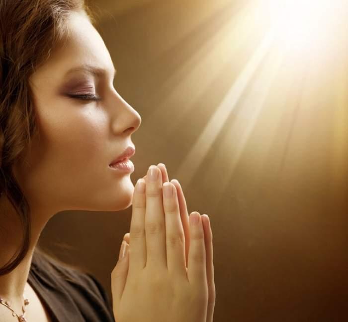 Femeie care se roagă în lumina soarelui