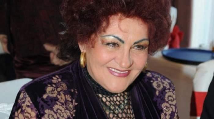 Elena Merișoreanu se află la un eveniment. Artista poartă o rochie mov și zâmbește larg.