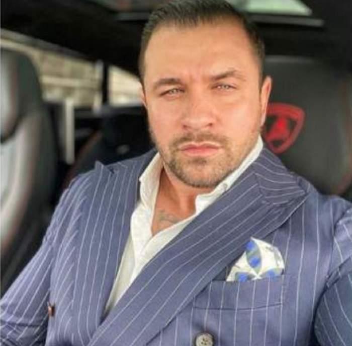Alex Bodi este in masina si poarta un costum albastru
