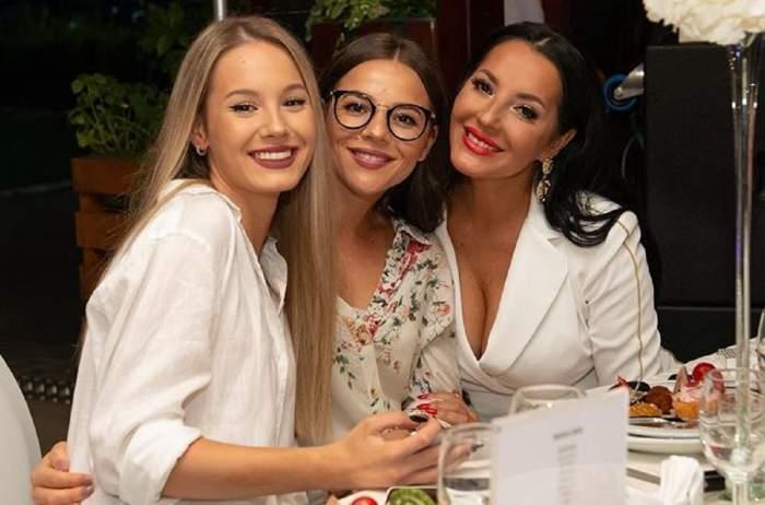 Angela Rusu și fiicele sale, Rebeca și Larisa. Cele trei stau la masă și sunt îmbrăcată în ținute albe
