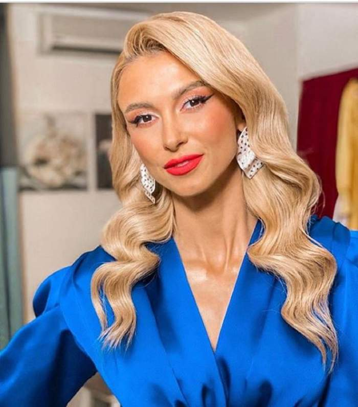 Andreea Balan poarta o rochie albastra si are parul ondulat