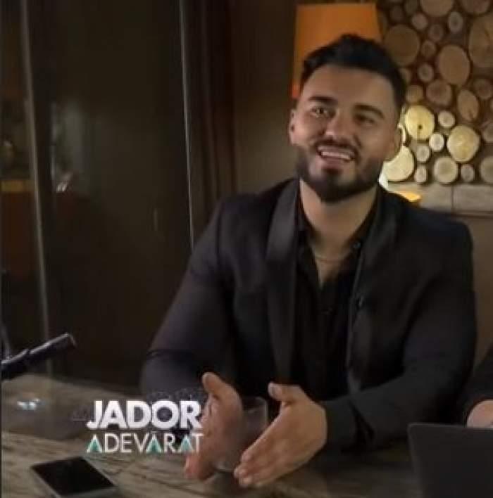 Jador, surprins în dreptul unei filmări, zâmbitor, în costum negru