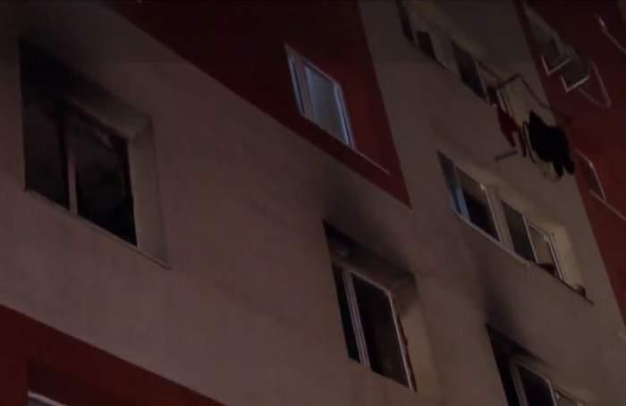 Blocul este afectat din cauza incendiului, se observa urmele de fum pe fereastra apartamentului