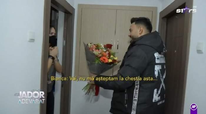 Jador îi livrează flori unei tinere. Artistul e îmbrăcat cu o geacă neagră și se află în fața ușii clientei, ținând un buchet mare și colorat în mână.