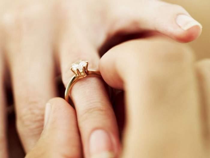 Imagine cu un mana unui barbat care ii aseaza inelul de logodna pe degetul unei femei