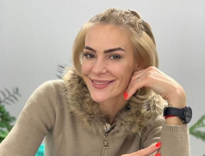 Roxana Ciuhulescu e îmbrăcată cu un pulover crem închis. Blondina zâmbește larg și are o mână la nivelul bărbiei. Vedeta poartă un ceas negru.