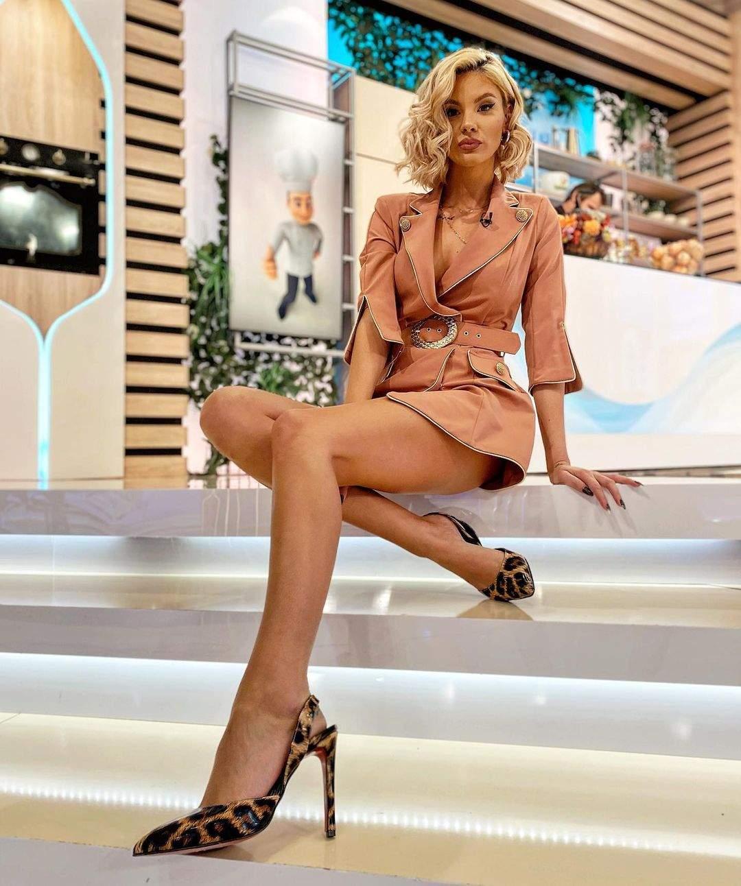 Ramona Olaru sta pe scarile din platou, poarta o rochie roz si pantofi cu toc