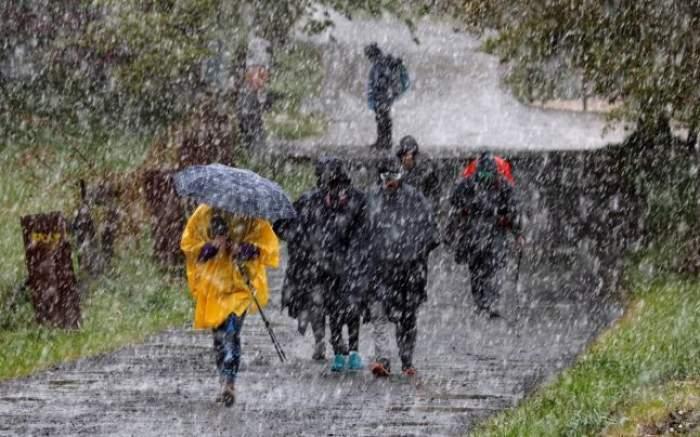 Mai mulți oameni, îmbrăcați de iarnă, aleargă prin ploaie, cu umbrelele în mână