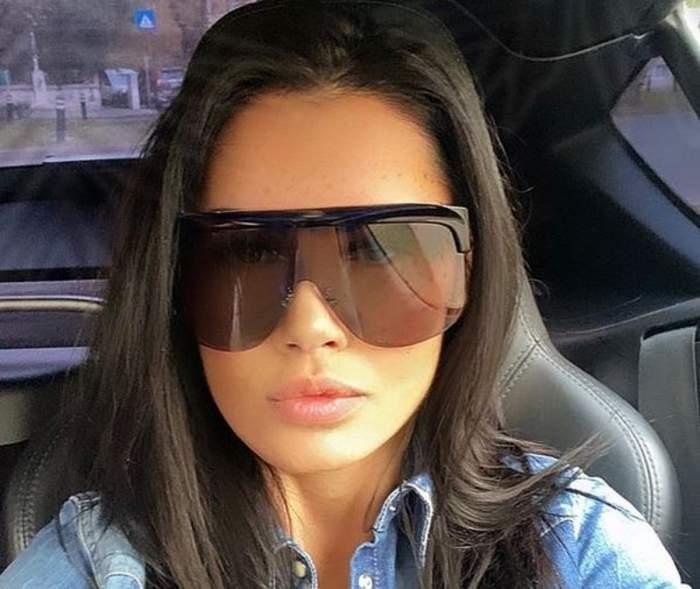 Oana Zăvoranu se află în mașină. Artista poartă ochelari de soare și geacă de blugi.
