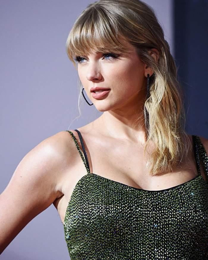 Taylor Swift este la o gala, poarta o rochie verde inchis cu bretele si are parul prins in laterale