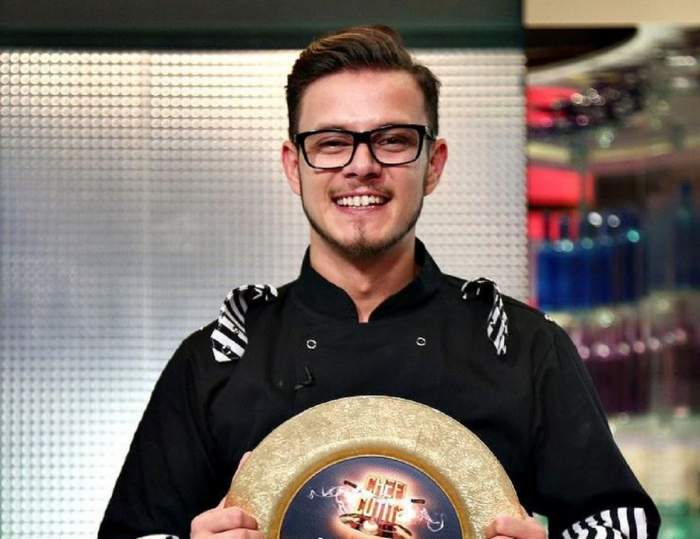 Ionuț Belei se află la Chefi la Cuțite. Tânărul poartă uniformă neagră de bucătar și ține în mâini marele premiu de 30.000 de euro.
