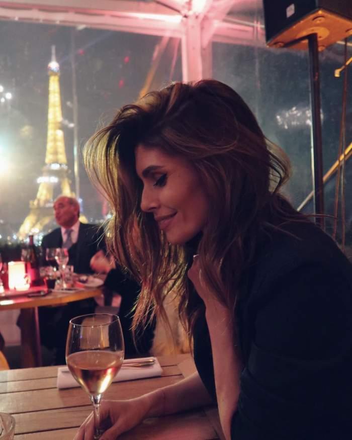 Sanziana Negru este la o cafenea din Paris, are un pahar cu vin alb in fata si zambeste