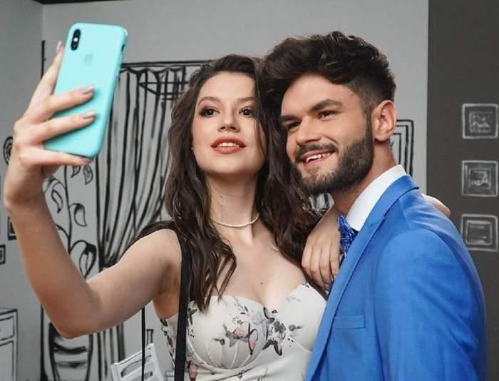 Cleopatra Stratan și Edward Sanda își fac un selfie. Ea poartă un top alb cu fluturi, iar el un costum bleu.
