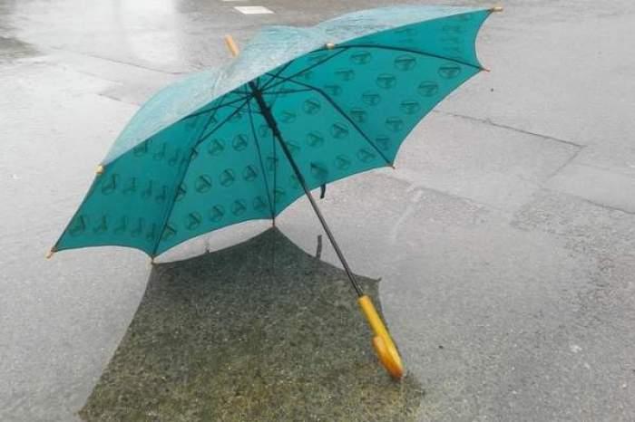 O umbrelă albastră, pe o stradă plouată