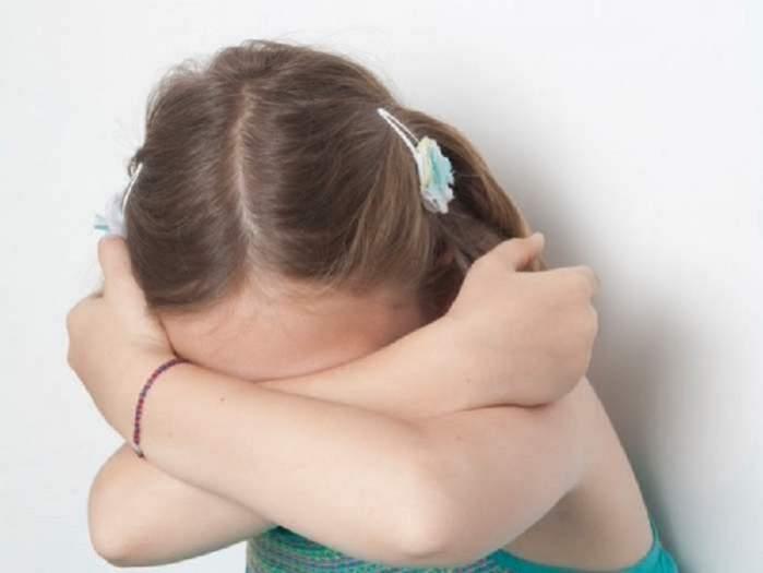 O fetiță are brațele încrucișate și își ascunde fața. Copila poartă un maiou turcoaz și are două clame prinse în păr.