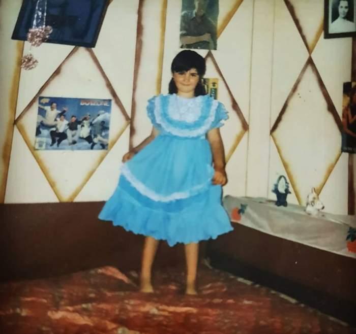 Claudia Radu in copilarie, purta o rochie albastra cu volane si area parul prins, sta in picioare pe pat