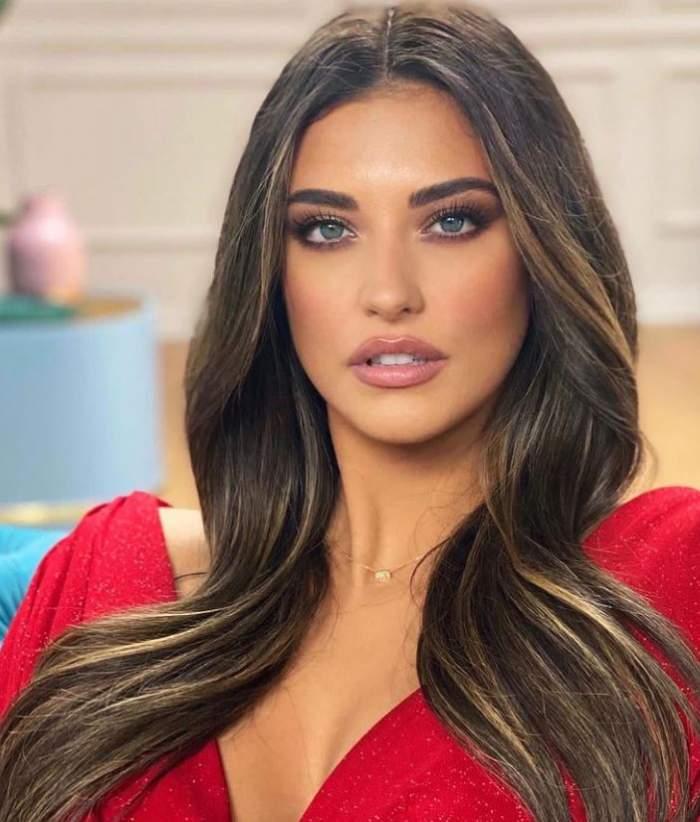 Antonia poarta o rochie decoltata rosie si are parul aranjat pe umeri