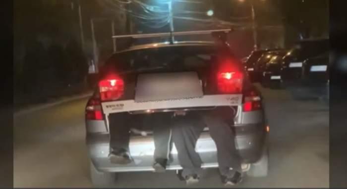 Sotul soferitei si prietenul lui stau in portagajul masinii, cu picioarele in afara