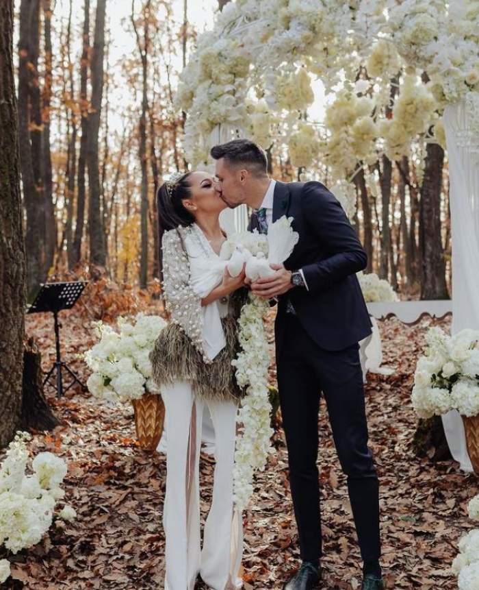Vladuta Lupau si sotul ei sunt intr-o padure amenajata de eveniment, poarta un costum alb si el unul negru,se saruta