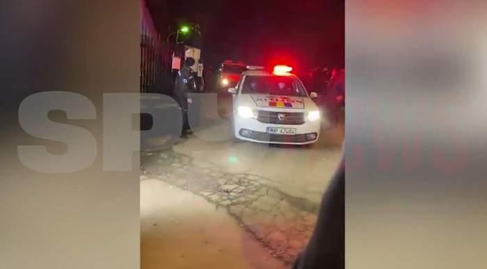 O mașină de Poliție iese pe poarta cimitirului în care a fost înmormântat Nicolae Duduianu