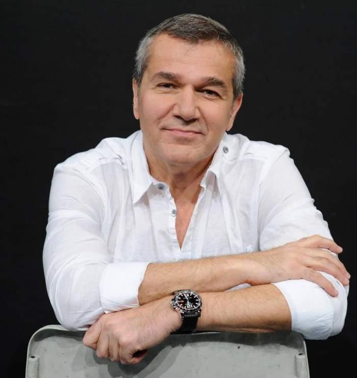 Dan Bittman, fotografiat zâmbitor, în cămașă albă, stând pe scaun