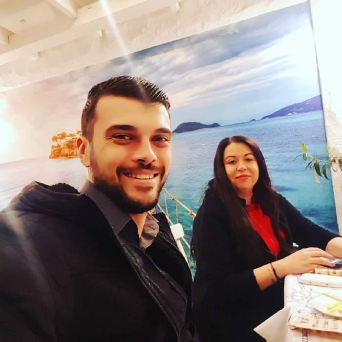 Oana Roman și Marius Elisei se află la un restaurant. Ea poartă o bluză roșie, iar el o haină neagră.