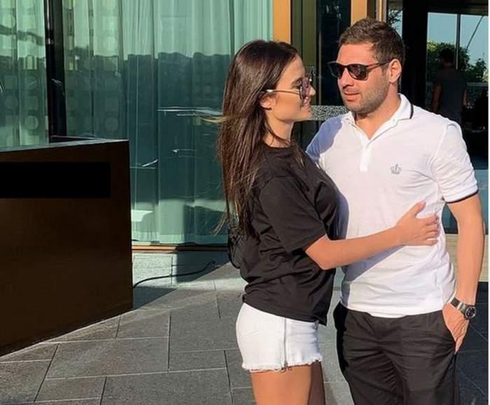 Adi Popa și iubita lui se află pe stradă. El poartă un tricou alb și pantaloni negri, iar ea un tricou negru și pantaloni albi.