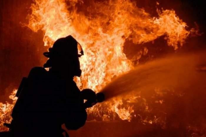 Imagine cu un pompieri in timp ce stinge un incendiu