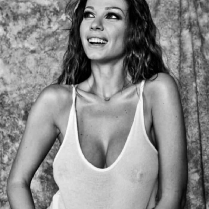 Iuliana Luciu, fotografiată zâmbitoare, într-o ținută albă, transparentă și decoltată