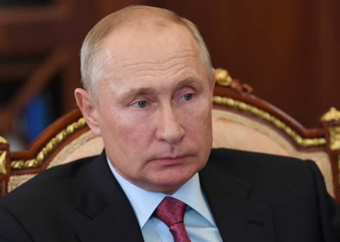 Vladimir Putin sta pe un scaun, poarta costum cu cravata rosie