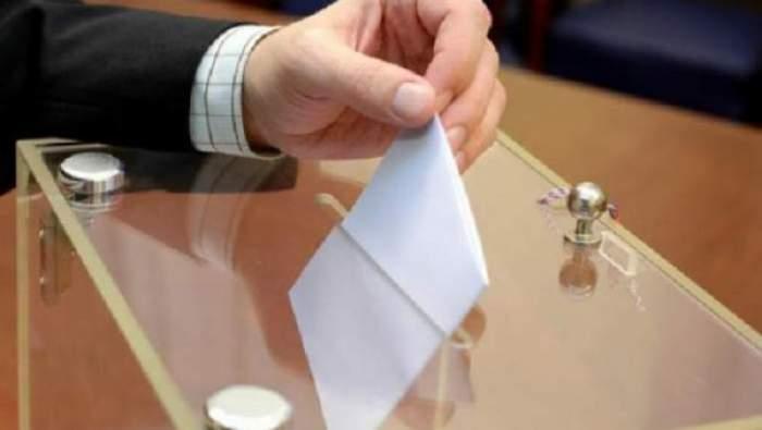 Un bărbat care pune votul în urnă