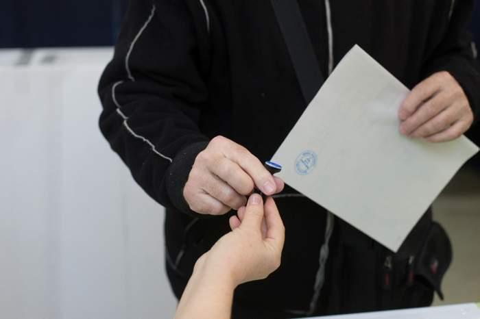 Imagine cu un cetatean caruia i s-a dat buletinul de vot si stampila