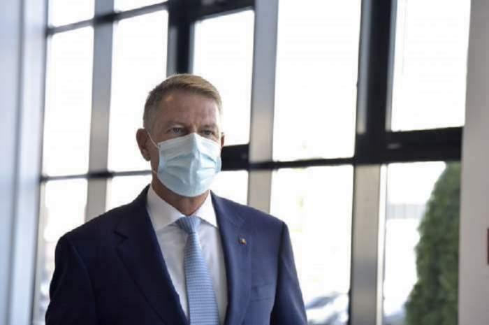 Klaus Iohannis poartă un costum albastru închis cu o cămașă albă pe dedesubt. Acesta poartă mască de protecție.