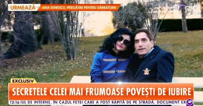 Petre Roman și Silvia Chifiriuc stau pe o bancă. Amândoi poartă câte o haină albastră, iar artista are la ochi și ochelari de soare. Cei doi se află la Sinaia.