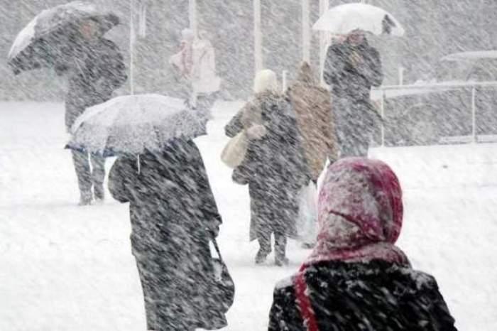 Oameni pe stradă cu umbrele în timp ce ninge!