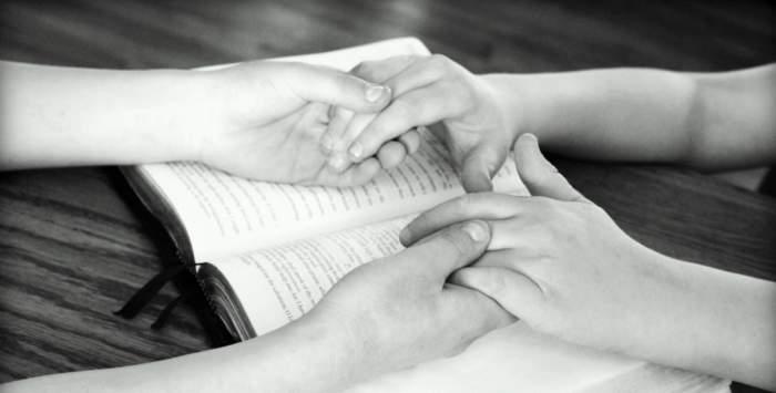 Două persoane se țin de mâini deasupra unei cărți religioase pentru a se ruga