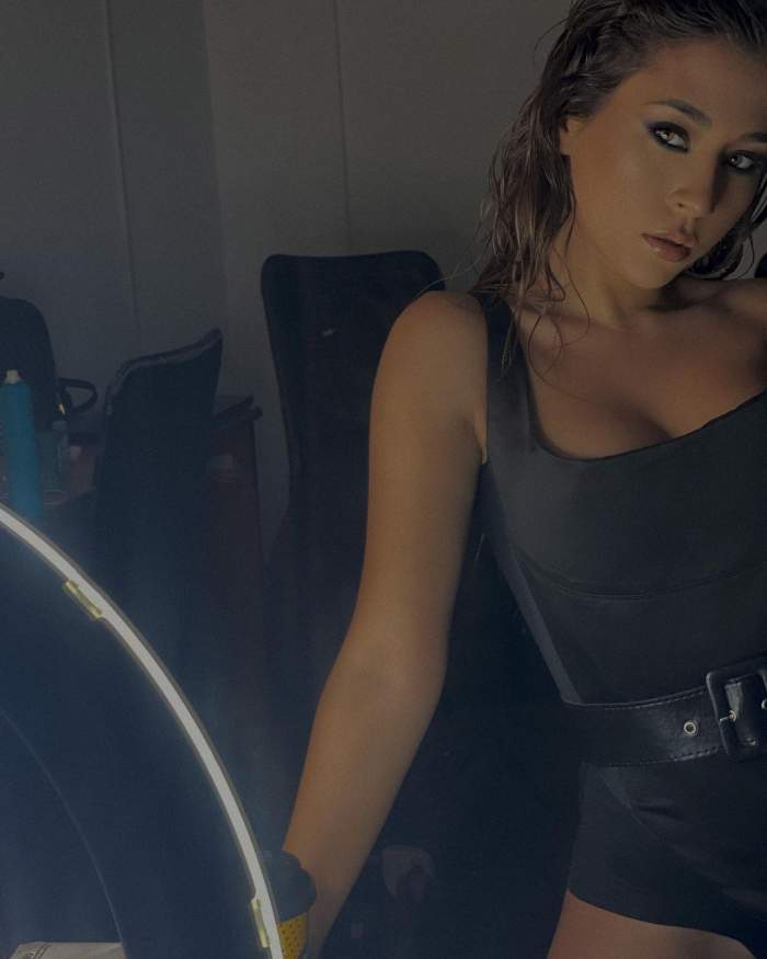 Nicole Cherry poarta un corset negru, este machiata strident, are parul desprins pe spate