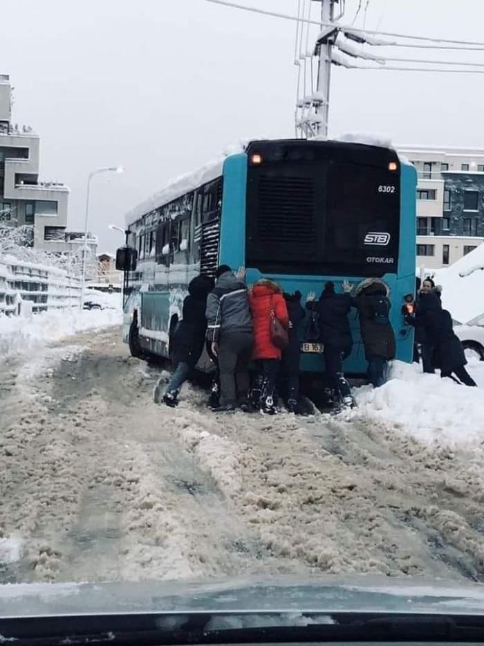 Imaginea zilei! Mai mulți călători împing un autobuz STB, ca să îl scoată din zăpadă