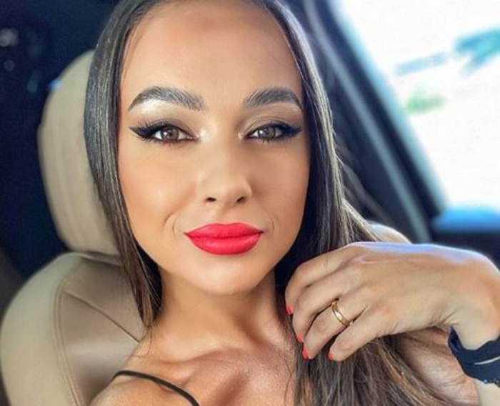 Vlăduța Lupău într-un selfie. Cântăreața are un zâmbet discret pe buzele frumos colorate în roșu și își ține mâna prin păr.