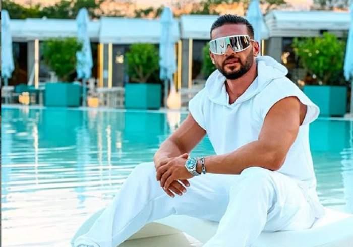 Dorian Popa s-a fotografiat pe marginea unei piscine, într-o ținută complet albă, asortată cu ochelari de soare masivi