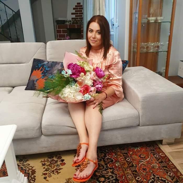 Oana Roman, îmbrăcată într-o rochie, stă pe canapea în timp ce ține un buchet de flori în brațe
