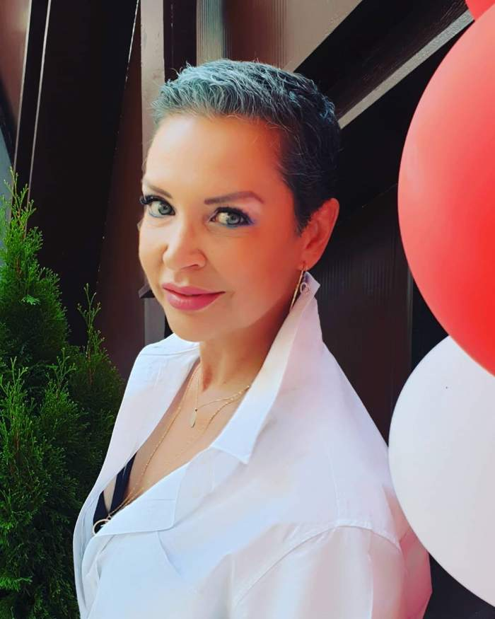 Eugenia Șerban, tunsă scurtă, zâmbitoare și purtând o cămasă albă, după ce a învins cancerul