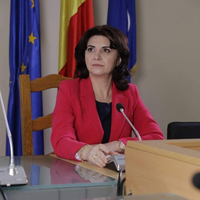 Monica Anisie, purtând un sacou roși, în cadrul unei conferințe