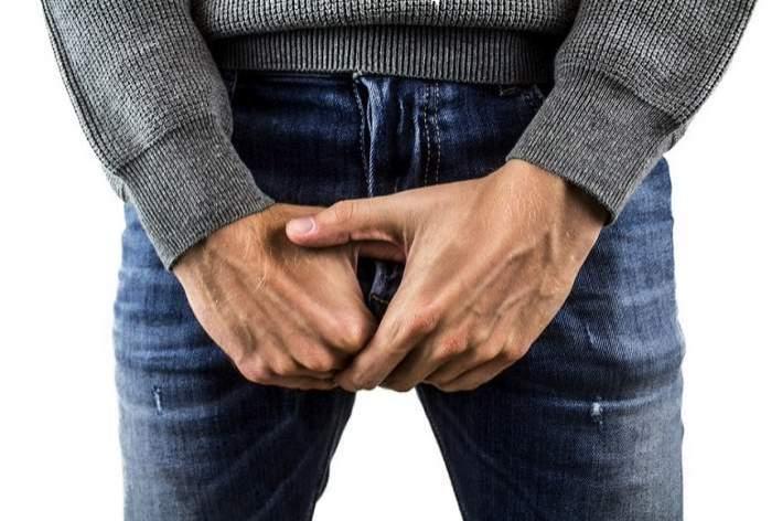 bărbat îmbrăcat cu blugi ţine mâinile în zona genitală