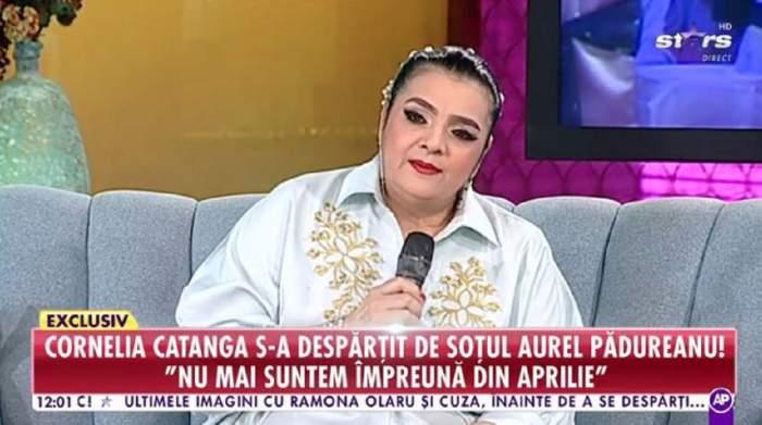 """Cornelia Catanga pe canapea, la """"Star Matinal"""". Artista e îmbrăcată într-o cămașă albă și ține microfonul în mână. Are părul prins în coc."""