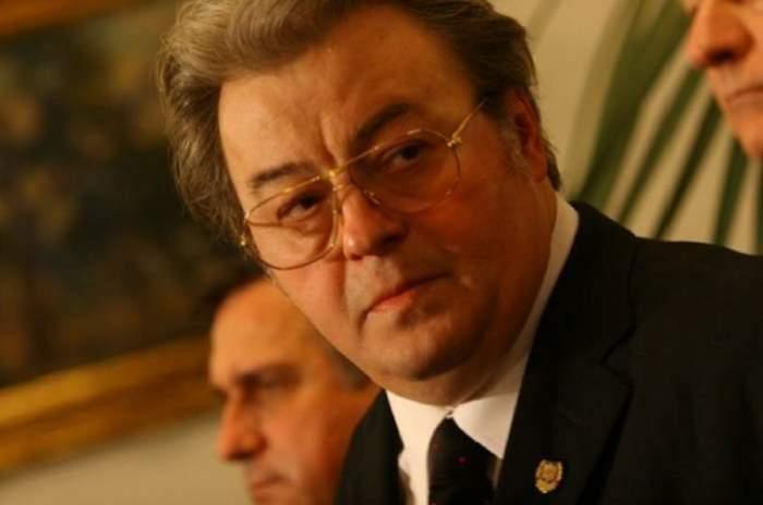 Corneliu Vadim Tudor. E îmbrăcat la costum și poartă ochelari de vedere.